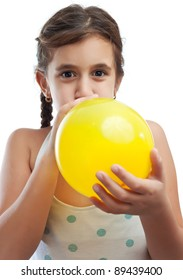 Latin girl blowing a yellow balloon isolated on a white background