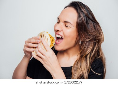 Latin girl holds an arepa in her hands ready to eat it, Arepa stuffed with chicken