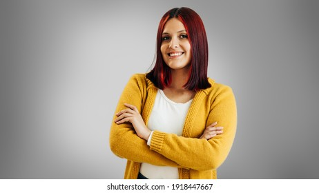 Latin girl with red hair and yellow jacket crossing her arm on gray background