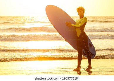 latin hispanic woman with blonde afro curls holdian a surfboard on beach
