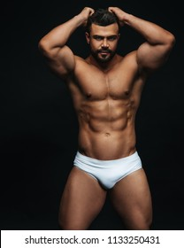 Latin hunk in white swimwear at black background
