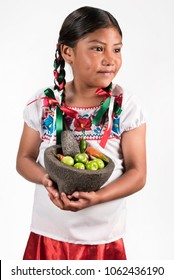 Latin little girl making hot salsa Shot of cute girl with a mortar and ingredients for salsa