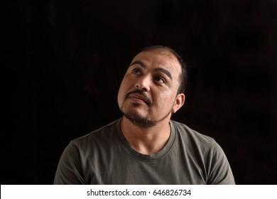 Latin man looking up on black