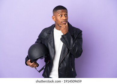 Latin man with a motorcycle helmet isolated on purple background having doubts and thinking
