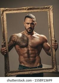Latin Man with muscular body holds a frame and looks seriously. Muscular latin lover. Handsome brutal man on gray background. Portrait of brutal handsome male model