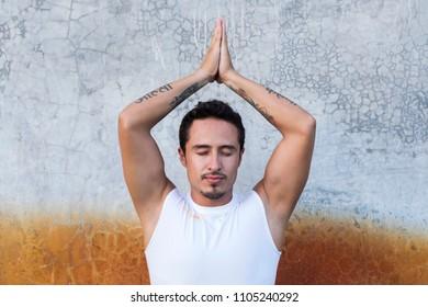 Latin man practicing meditation. Tattoos in Sanskrit meaning: Ahimsa (Non violence) and Karuna (compassion)