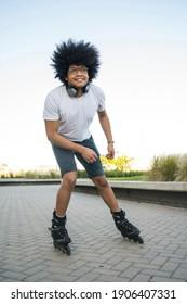 Latin man rollerskating on the street.