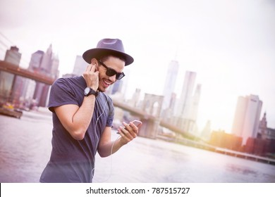 Latin man walking in New York while listening music and texting with his smart phone