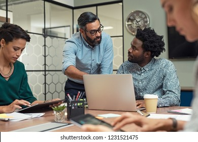 Latin mature manager discussing with his colleague online data in front of laptop. Serious businessman training employees in job. Creative multiethnic team working together with boss in meeting room.