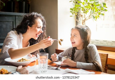 Latin mom and daughter eating together lunch at restaurant, multiethnic family having fun