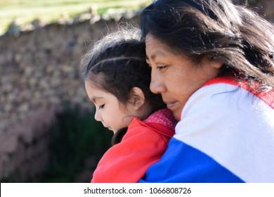 Latin mom hugging her little daughter outside.