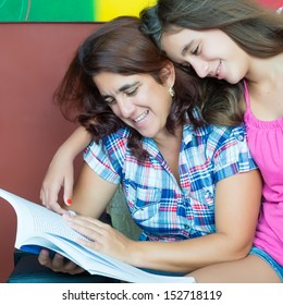 Latin mother and her beautiful teenage daughter reading a book at home