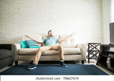Latin single man relaxing alone in the living room of his new apartment with her arms open