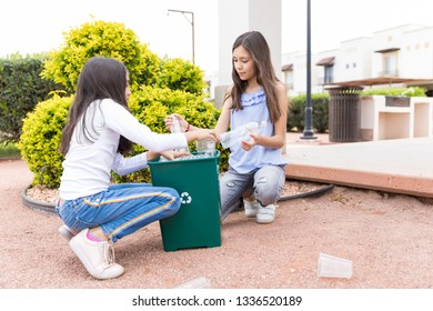 Latin sisters collecting used plastic bottles into recycling bin at park