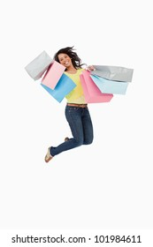Latin student jumping with shopping bags against white background