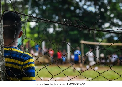 latin teen leaning on fence watching soccer/football in Guatemala
