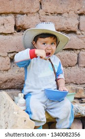 Latin toddler boy eating in the countryside.