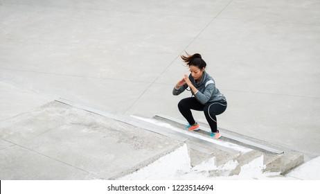 Latin urban sporty woman training. Female athlete doing squat jumps on urban stairs.