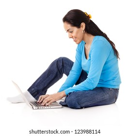 Latin woman in blue top sitting on floor with laptop