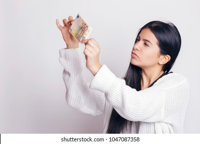 Latin woman checking a fifty euro banknote. Indoors, over a white background.