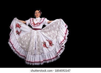 Latin woman dancer wearing dress from the city aguascalientes Mexico, black background, with white dress with wine-colored ribbons, moving her skirt and smiling