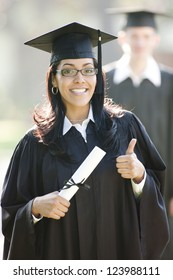 Latin woman graduate with thumbs up in graduation cap and gown and diploma
