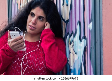 Latin woman with headphones and mobile phone leaning on public wall with graffiti not subject to copyright