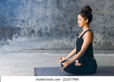 Latin woman practicing meditation against a urban background