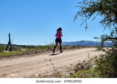 Latin woman running a race on a rural road during summer. Crosscountry race. Copy space.