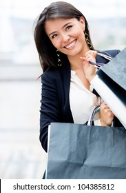 Latin woman shopping holding bags and looking happy