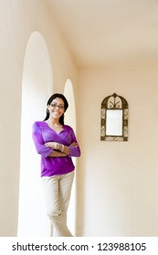 Latin woman standing next to arches with mirror on wall, looking to camera with glasses and purple top and arms folded