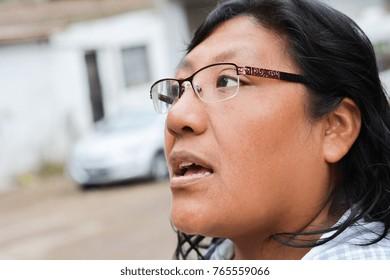 Latin woman talking outside.