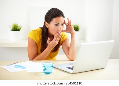 Latin worker in yellow clothes looking shocked in her workplace