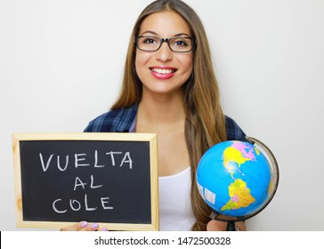 "Latin young female teacher holding globe and blackboard with spanish written ""Vuelta al cole"" (Back to school)."