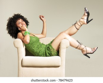 Latin young woman talking with telephone in a sofa.