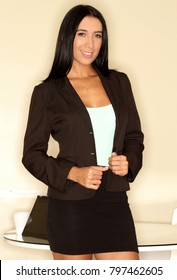 Latina business woman smilng in suit at the office