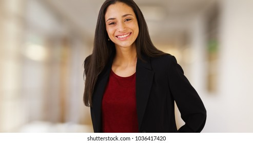 A Latina businesswoman poses for a portrait in her office hallway