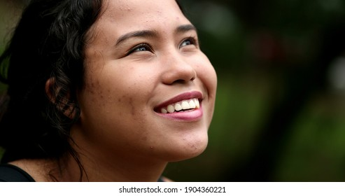 Latina girl looking at sky smiling. Hispanic young woman close-up face with HOPE and FAITH