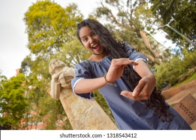 Latina girl shows us the size of something by means of her hands while walking in a park near Marco Polo