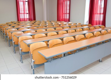 """Latina, Italy - april 22, 2011: Empty classroom with chairs, desks and chalkboard. Classrooms of the University branch of Rome """"La Sapienza""""."""