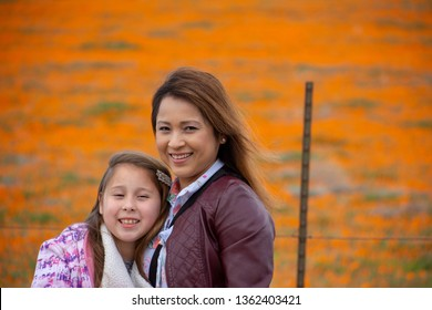 Latina Mother and Daughter in front of desert California Poppy field orange bokeh during the Spring