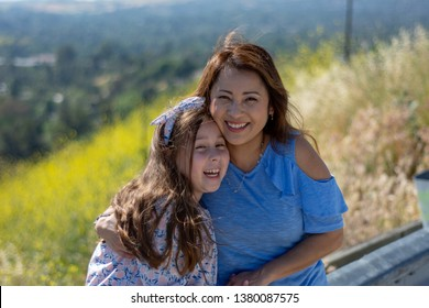 Latina Mother and Daughter Smiling and laughing on a hill in front of yellow flowers in the Spring or Summer