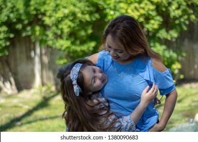Latina Mother and Daughter Smiling and laughing outside in back yard in the Spring or Summer