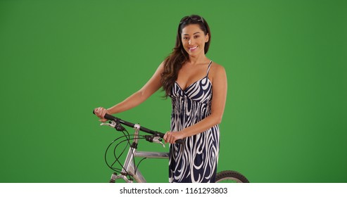Latina woman in fashionable sundress standing with bicycle on green screen