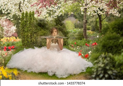 latina woman sitting in flower park in big tulle skirt blowing glitter from a story book