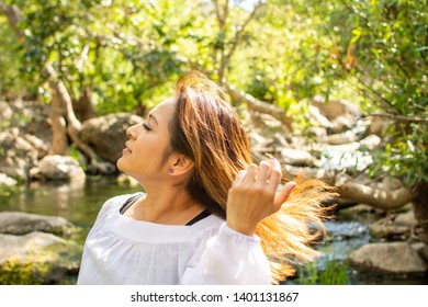 Latina woman throwing her hair back with her hair in the sun in front of woods and a stream in the shade in the Spring