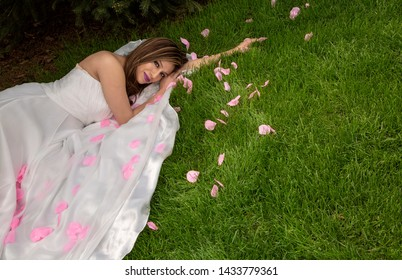 latina woman in white gown laying in grass and pink petals