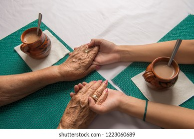 Latin-Mexican Grandma and grand daughter drinking hot chocolate and having a conversation, holding their hands on the table (Young girl receiving advice from her grandma)