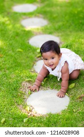 Latino baby girl beginning or learning to crawl on a green lawn with many steps to walk on.