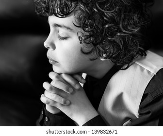 Latino boy daily devotional. Hispanic child praying and praising God. Hope in a young kid. Religious image
